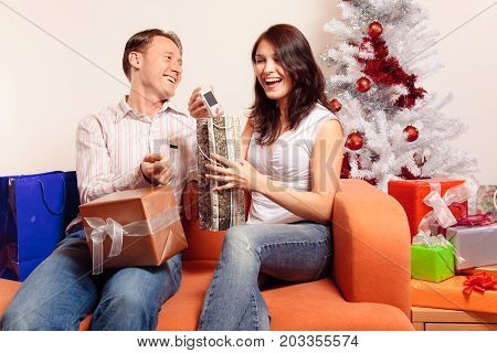a young couple is sitting on the couch and exchanging christmas gifts. in this pic, she got a new mobile phone and seems quite happy with it.