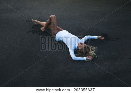 Vacation travel concept. Beautiful sexy girl in white swimwear lying on beach with dark black sand