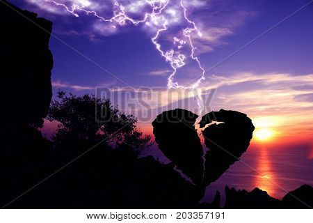 Lightning down to the broken heart-shaped stone on a mountain with purple sky sunset background.Silhouette Valentine background concept.