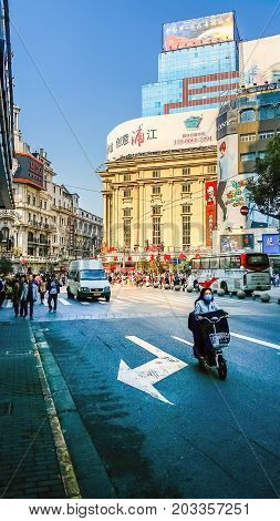 Shanghai, China - Nov 6, 2016: On Hubei Road. Intersects with Nanjing Road Pedestrian Street ahead. Traffic flow with people walking on the road.