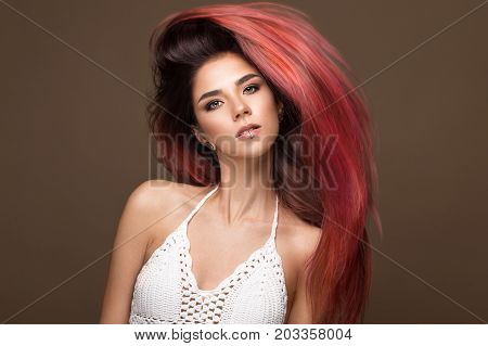 Beautiful pink-haired girl in move with a perfectly smooth hair, and classic make-up. Beauty face. Picture taken in the studio.