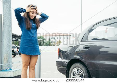 sad woman standing near car with scratch on parking