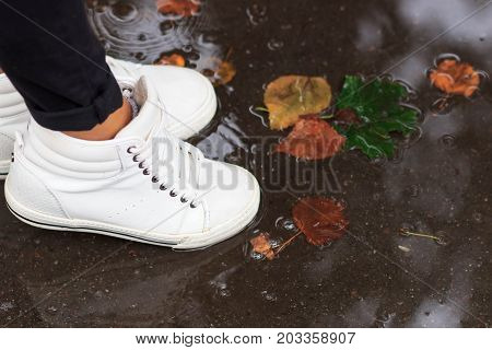 legs in white shoes jumping in the autumn puddles. Autumn leaf