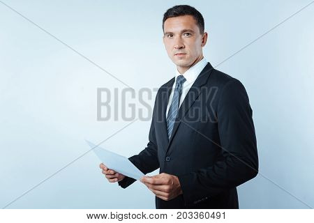 Successful entrepreneur. Handsome nice confident man holding a sheet of paper and looking at you while standing against blue background