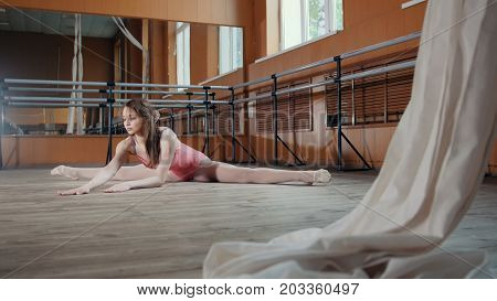 Young athletic acrobatic girl sits on a splits, circus artist