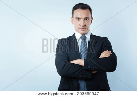 Confident businessman. Serious nice handsome man standing cross armed and looking at you while showing his confidence