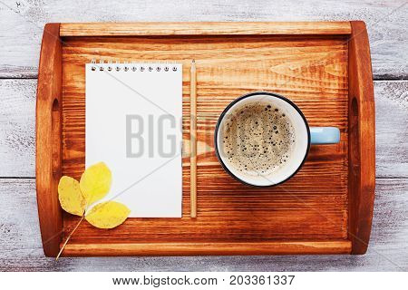Morning coffee and empty notebook on wooden tray top view. Cozy autumn breakfast. Fall bucket list. Flat lay style.