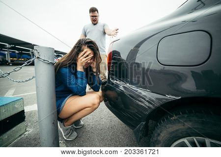 man shout on woman because of scratched car, sad woman looking on car damage