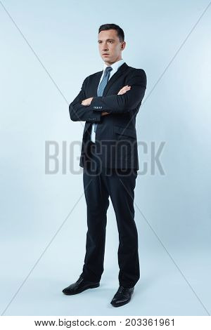 Confident businessman. Serious nice handsome man standing against blue background and crossing his arms while showing his confidence