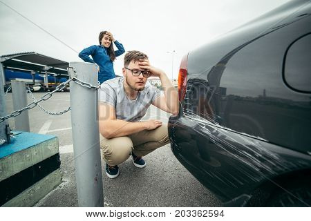 sad man looking on car scratch, woman stand behind him with sorrowful look