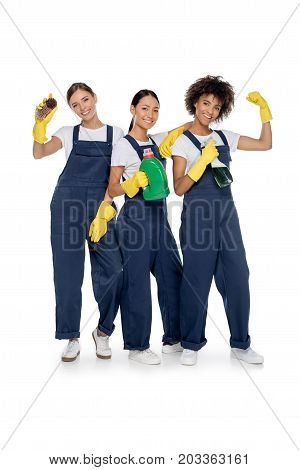 smiling multicultural cleaners with cleaning supplies looking at camera isolated on white