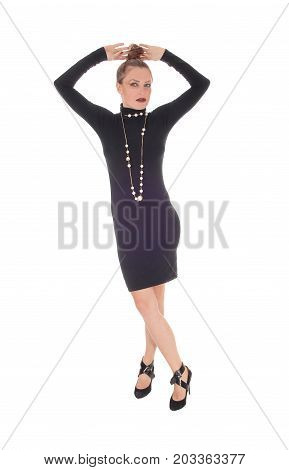 A beautiful young Caucasian woman in a black dress and necklace with her arms up over her head isolated for white background