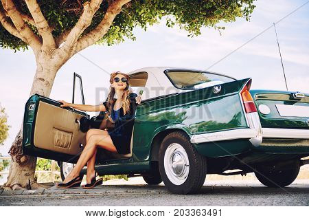 La Vila Joiosa, Spain - May 28, 2017: Beautiful happy woman sitting in a Triumph Herald car. It is a small two-door car introduced by the Standard-Triumph Company of Coventry in 1959