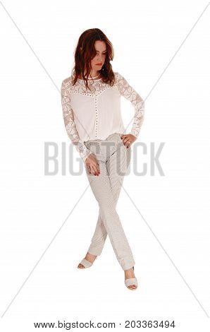 A beautiful young woman in a lace blouse and brunette hair standing in dress pants with her legs crossed isolated for white background
