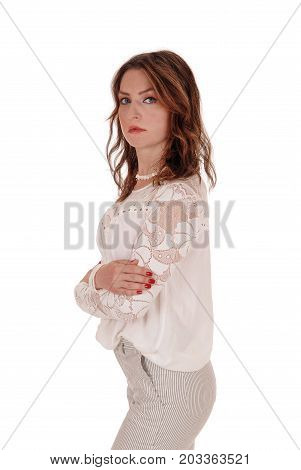 A beautiful young woman in a lace blouse and brunette hair standing in dress pants in profile isolated for white background