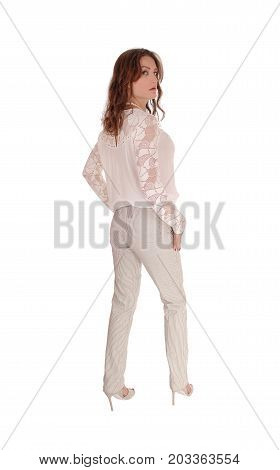 A beautiful young woman in a lace blouse and brunette hair standing in dress pants from the back isolated for white background