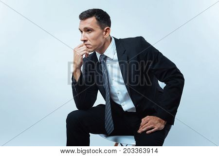 Thoughtful pose. Nice thoughtful smart man sitting on the chair and holding his chin while thinking about his work