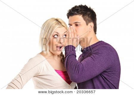Man whispering a secret to a surprised young woman isolated on white background