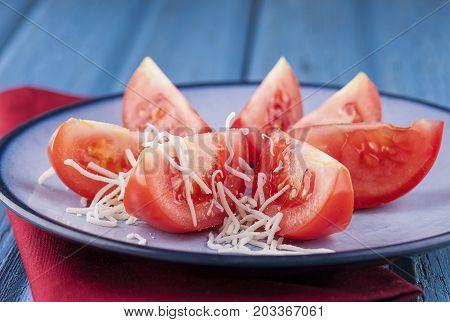 Shredded cheese on tomato wedges. Shredded white cheese layered on tomato wedges on a plate.