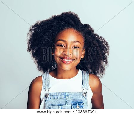 Cute Young African Girl Smiling Against A Gray Background
