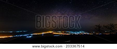 Panorama of Milky way over city lights long exposure photograph with grain