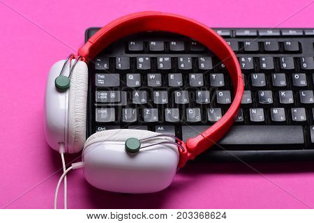 Headphones And Black Keyboard. Earphones In Red And White