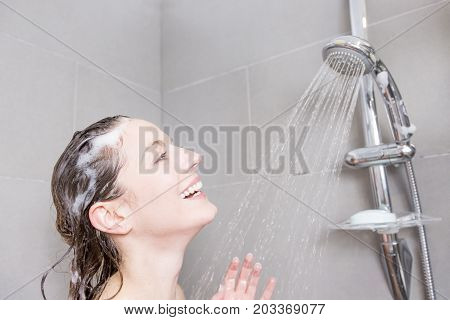 A beautiful Woman in shower washing hair with shampoo
