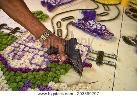 August 6 2017 Medellin Colombia: a farmer is gluing flowers one by one with hot glue to a large panel which will be presented at the flower festival parade