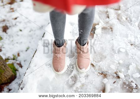 Close-up of girls legs on the snow. Adorable little girl having fun in beautiful winter park. Cute child playing in a snow. Winter activities for kids.