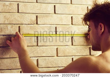 Man Measures Wall With Measuring Tape.