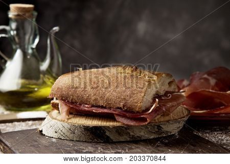 closeup of a typical spanish bocadillo de jamon, a serrano ham sandwich, on a rustic wooden table, next to a plate with some slices of serrano ham and a cruet with olive oil