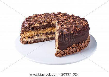 Isolated Chocolate Layered Cake With Nougat And Sponge Cake In The Cut On The Plate