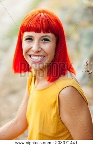 Portrait of red haired woman with yellow dress relaxed in a park