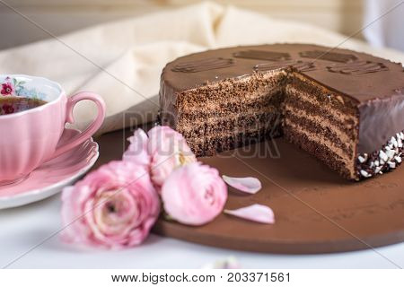 Delicious Chocolate Layered Cake With Nougat And Sponge Cake In The Cut. Served Flowers Roses And Pi
