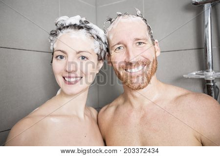 A Young couple washing their heads in the shower