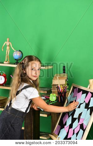 Schoolgirl With Interested Face Stands By School Stationery
