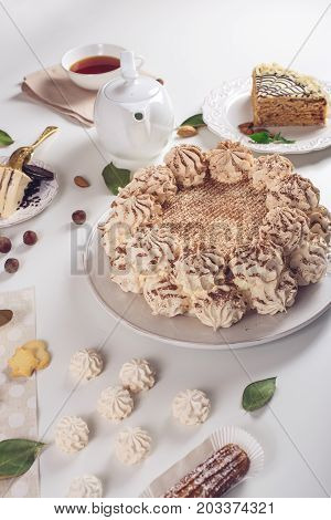 Decorated Dessert Table Where The Cake With Meringue, Layered Pieces Of Cake. Arrangement Of Delicio