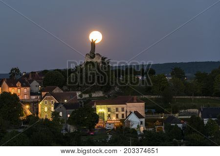The statue of Pope Urbanus 2 in the Champagne village of Chatillon-sur-Marne in the Champagne district in France rising of the full moon.