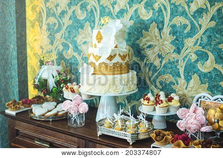 Luxury Wedding Candy Bar With A Beautiful White Cake Decorated With Gold Ornaments. Concept Of Chic
