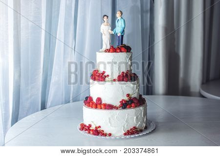 Wedding Cake With Figurines Of The Bride And Groom On Top Decorated With Strawberries On The Tiers