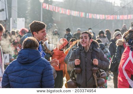 PERNIK, BULGARIA - JANUARY 27, 2017: Teen boy carrying heavy traditional bells is complaining about their weight at Surva, International Festival of the Masquerade Games