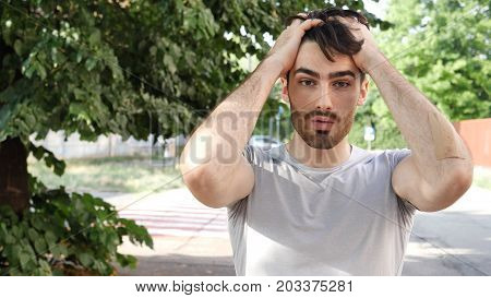Surprised, unsure, shocked handsome young man looking at camera outdoor in city