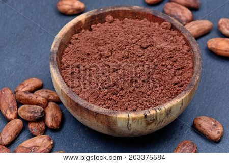 Bowl with cacao powder and beans on blue slate