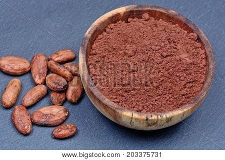 Cacao beans with powder on slate close-up