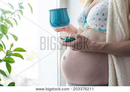 A Pregnant Woman With A Big Belly Holding A Coffee And A Cigarette. Concept Of Smoking And Bad Habit