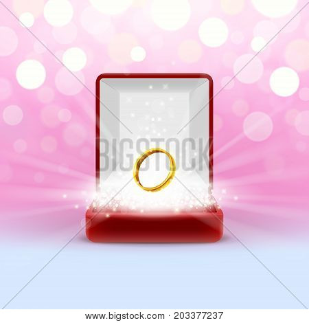 Open jewelry box with gold wedding ring glowing from inside on abstract bokeh background. Engagement gift