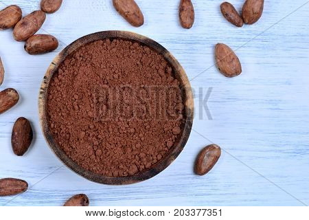 Bowl with cacao powder and beans on table close-up