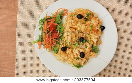 Traditional portuguese food Bacalhau on white plate at restaurant wooden table background. Codfish dish made with dried and salted cod, eggs, potato chips, olives. Served with small side green salad.