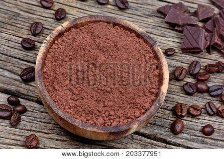 Bowl with cacao powder and coffee beans on rustic wooden table