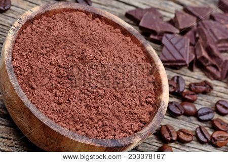 Bowl with cacao powder with coffee beans and dark chocolate on table
